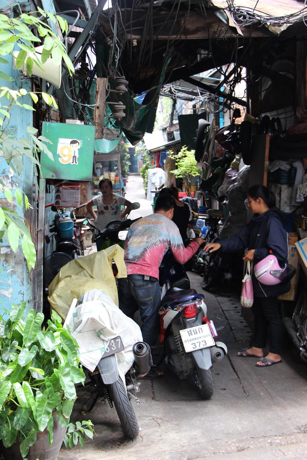 Een scooterrijder baant zijn weg door de smalle straatjes van Chinatown Bangkok
