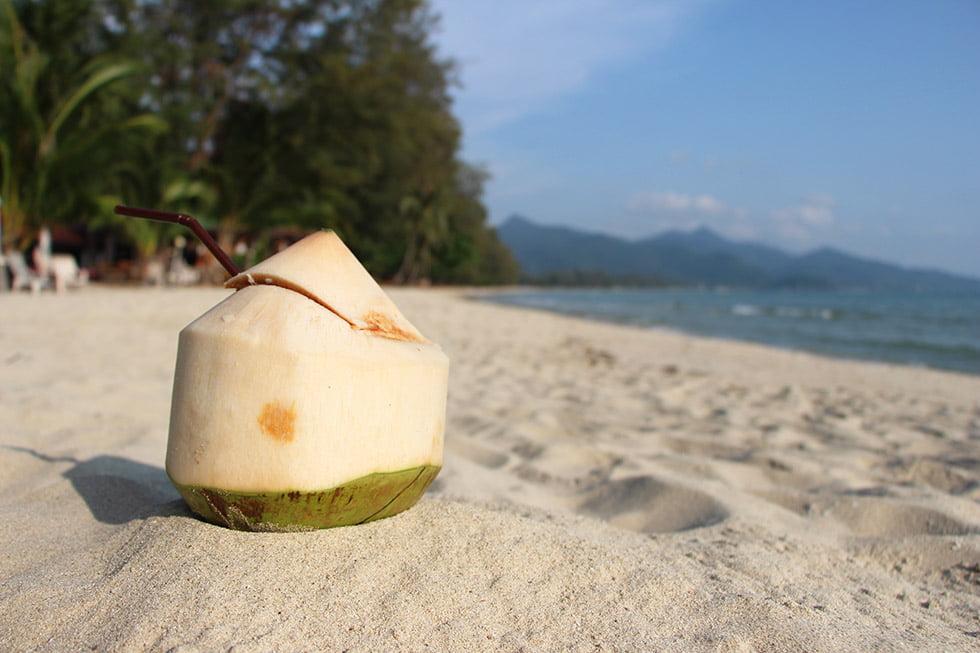Kokosnoot drinken op een leeg strand