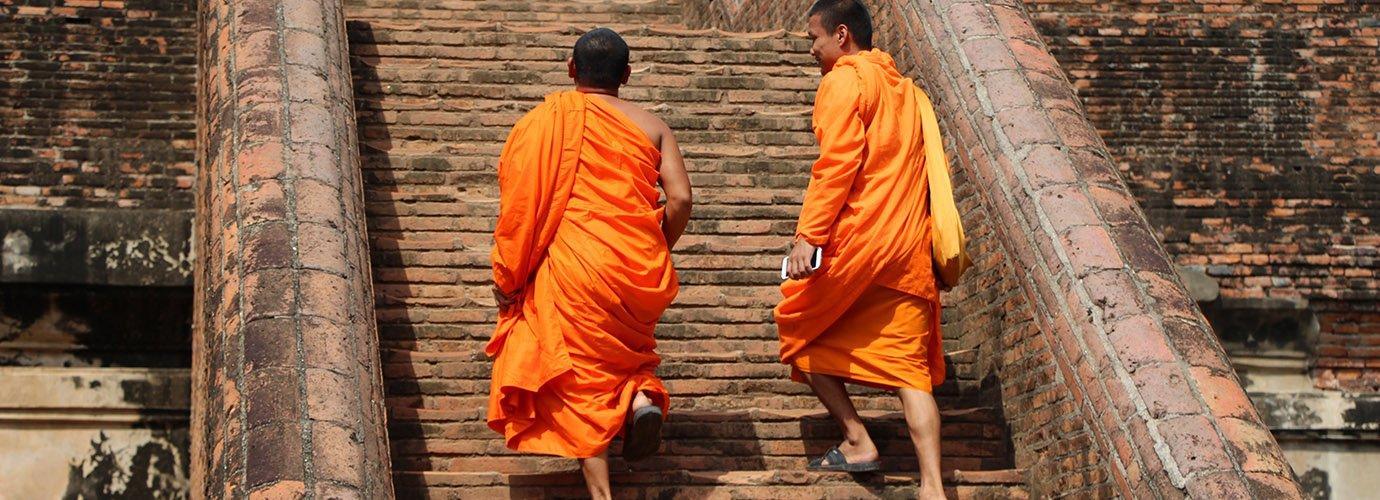 Monniken in oranje gewaad bewandelen eeuwenoude treden
