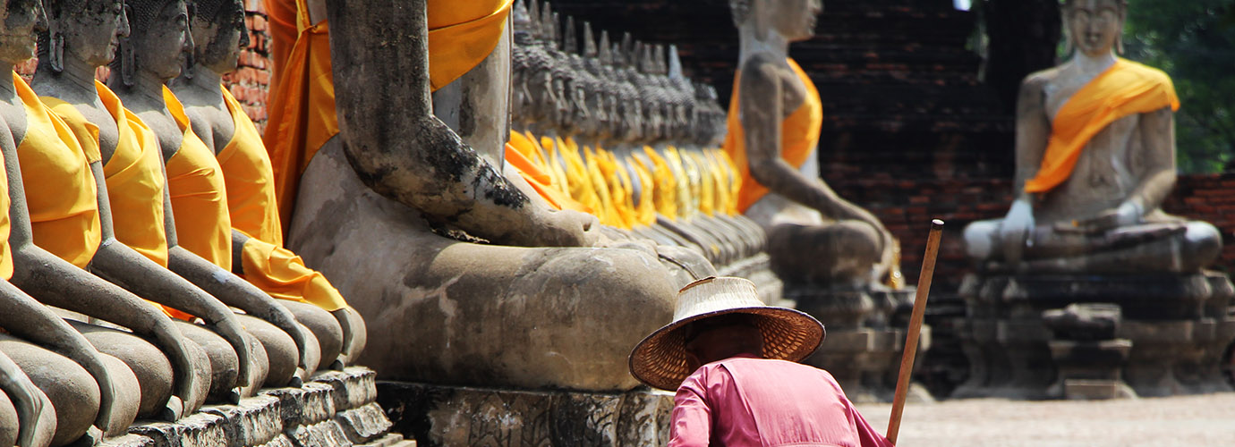 Een schoonmaakster bij de Wat Chai Mongkon in Ayutthaya