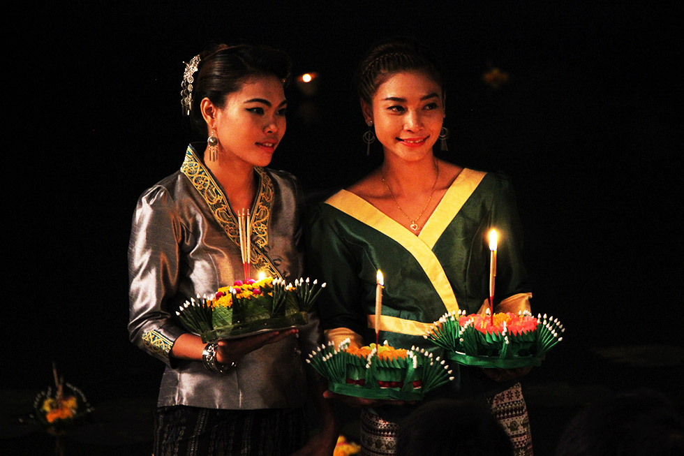 Thaise vrouwen poseren met hun krathong voordat ze hem te water laten